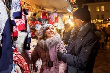 shopping, winter holidays and people concept - happy senior couple at christmas market clothing...