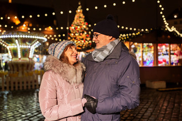 love, winter holidays and people concept - happy senior couple at christmas market on town hall...