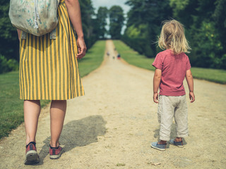 Mother and toddler standing on path in a park