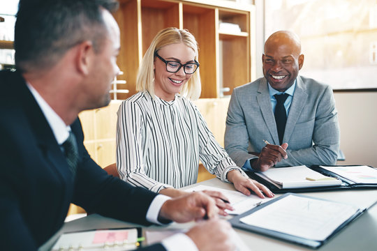Diverse group of businesspeople laughing during an office meetin