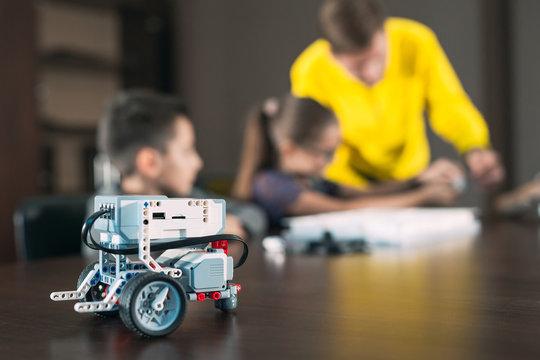 Kids creating robots with teacher. Early development, diy, innovation, modern technology concept.