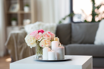 decoration, hygge and cosiness concept - candles burning on table and flowers at cozy home