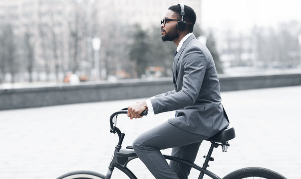 Afro businessman with headphones riding on bicycle to work