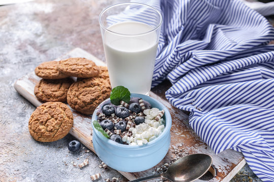 Cottage cheese with fresh blueberries, oatmeal cookies and milk. Healthy and tasty breakfast