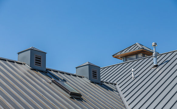 Ribbed Metal Roof and Cupolas Under Blue Skies