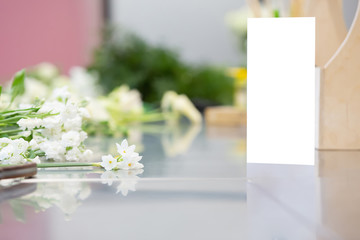 Beautiful white flowers and florist's tools lie on a glossy gray table. Concept of master class for making beautiful flower bouquets