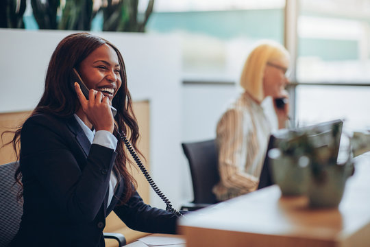 Laughing African American businesswoman working at an office reception desk