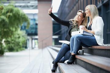 Arbeitskolleginnen machen ein Selfie beim Pausenkaffee