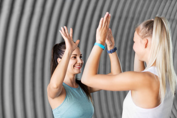 fitness, sport and healthy lifestyle concept - smiling young women or female friends with activity trackers making high five outdoors