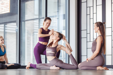 Positive young woman yoga instructor teaches her students to do eka pada rajakapotasana in spacious gym. Concept of healthy joints. Healthy lifestyle motivation after pilates fitness class in studio