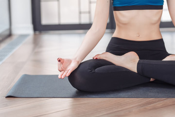 Young beautiful girl meditates in lotus pose sitting by large windows of a country house. Concept of relaxation and meditation. Ardha Padmasana exercise, meditating in Lotus pose with mudra gesture
