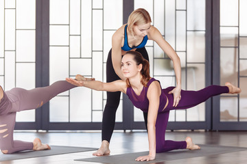 Beautiful young woman pilates instructor teaches her students how to do stretching exercises in the spacious gym. The concept of joint training and healthy lifestyle. Yoga class, workout