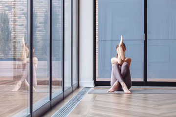 Relaxed young girl practicing yoga at home sitting near the large windows of a country house. Concept of meditation and relaxation