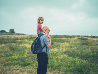 Little toddler riding on grandfather's shoulders in nature