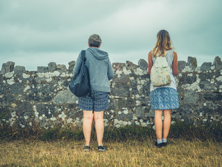 Young woman and her mother standing by wall on the coast in the fog