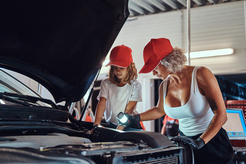 Mother is teaching her daughter how to fix broken car's engine at workshop.