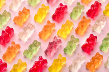colorful gummy bears pattern over pink background, close-up image