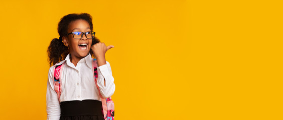 Schoolgirl Pointing Thumbs At Free Space On Yellow Background