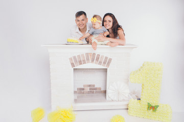 the child in the arms of his mother and father, who was soiled with food. A woman and man with a child in her arms eating cake on the fireplace