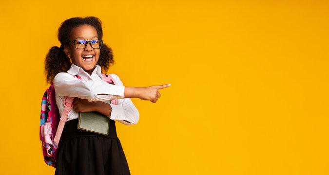 African American Schoolgirl Pointing Finger At Free Space, Studio Shot