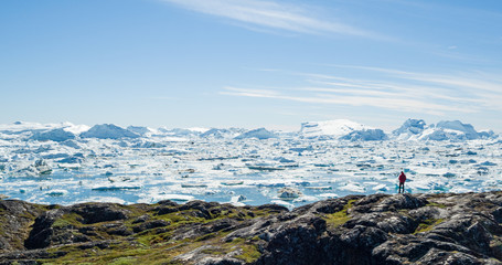 Travel wanderlust adventure in Arctic landscape nature with icebergs - tourist person looking at view of Greenland icefjord - aerial photo. Man by ice and iceberg, Ilulissat Icefjord.