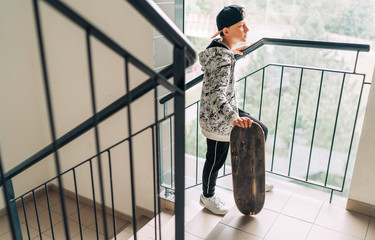 Teenager skateboarder boy with a skateboard going up by staircase home. Youth generation Freetime spending concept image.