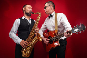 Group of two musicians, male jazz band, guitarist and saxophonist in classical costumes improvise on musical instruments in a studio on  red background