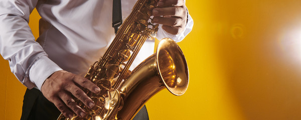 Professional musician saxophonist man in  white shirt plays jazz music on saxophone, yellow background in a photo studio, side view