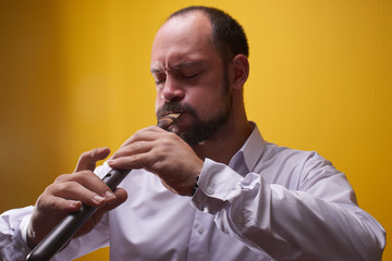 Professional musician man playing a pipe closeup in a yellow studio. Folk wind instrument, flute