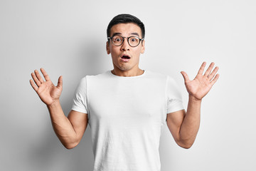 Shocked Asian man dressed in casual and glasses with open mouth and hands up looks to the camera . Surprised young Kazakh student guy on white studio background