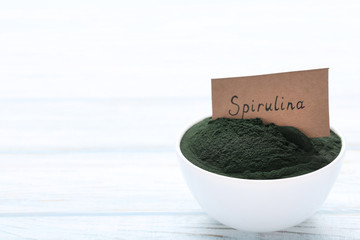 Spirulina powder in bowl on wooden table