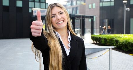 Confident young female manager outdoor in a modern urban setting giving thumbs up