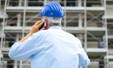 Engineer builder at construction site talking on the phone, back view portrait