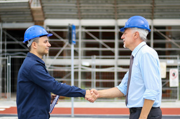 Two engineers shaking hands at a construction site