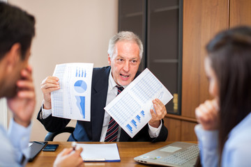 Angry manager showing bad financial results to some employees