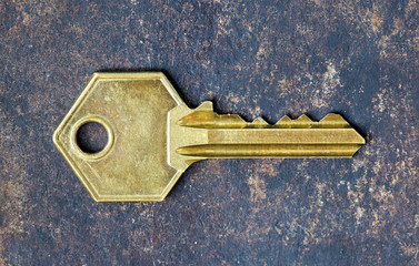 Old gold retro key on rusty metal background