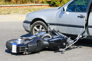 traffic accident, motorcycle collision with a car on city street