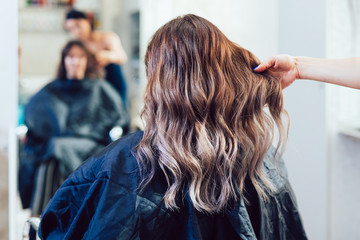 Photo sur Plexiglas Salon de coiffure Beautiful hairstyle of young woman after dying hair and making highlights in hair salon.