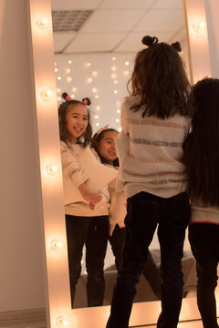 Happy sisters are playing in their room. Cute little girls near the mirror in the room in the evening dim light