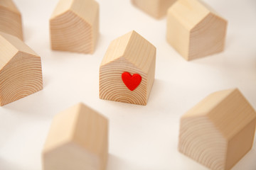 Miniature wooden house with red heart among others wooden houses
