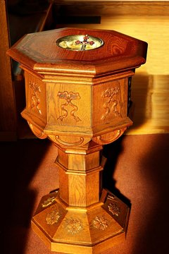 Sunbeams streaming in on old traditional eight sided wooden baptismal font with crucifix depicting holy trinity - concept of baptism in the name of the Triune God