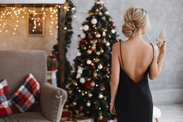 Beautiful and sexy blonde model girl with perfect body in the black dress with nude back keeps a glass of champagne and posing near the Christmas tree at interior decorated for New year