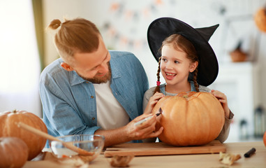 happy Halloween! family  father and child daughter cut pumpkin for holiday at home