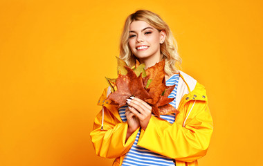 happy emotional girl with autumn leaves on colored yellow background