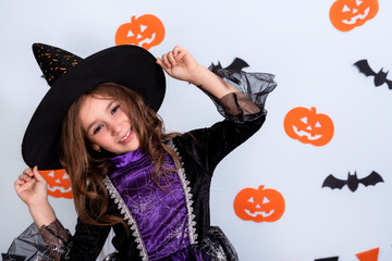 Happy little girl in costumes and makeup having fun on Halloween celebration over white background with bats and pumpkin Wall mural