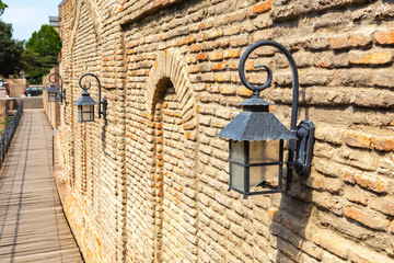 Old brick wall with cast iron lanterns