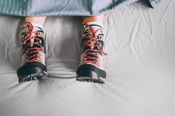 All time ready for trekking. Hiker sleeping in comfort trekking boots. Footwear on the bed sheet background concept image.