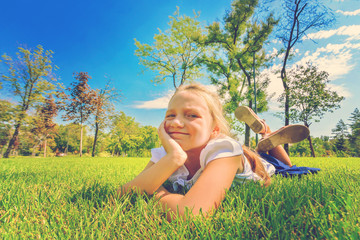 A young and beautiful girl lies on the green grass in the park and looks at the camera.