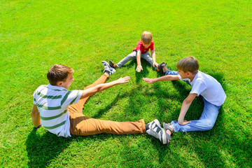 Three kids are sitting on green grass holding hands in a park.