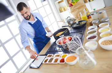 Man preparing delicious and healthy food in the home kitchen